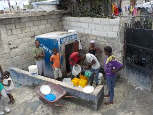 People queued at water pump with buckets